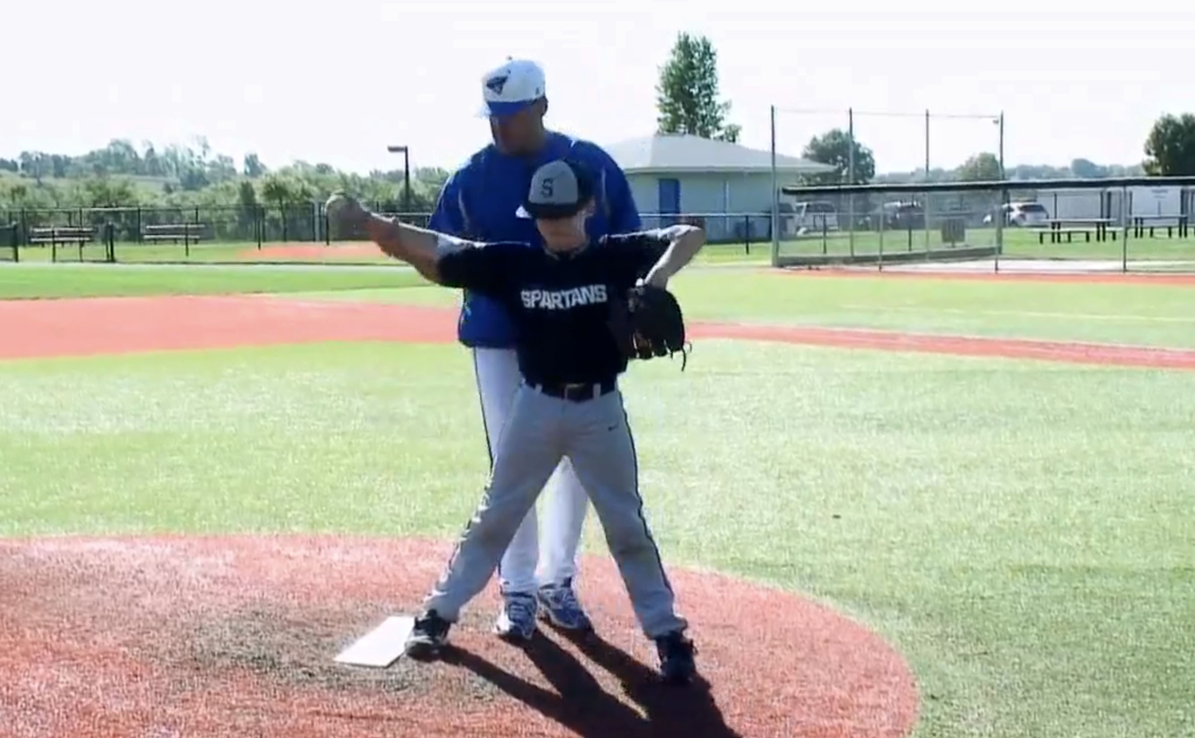 Coach positioning elbow for pitching