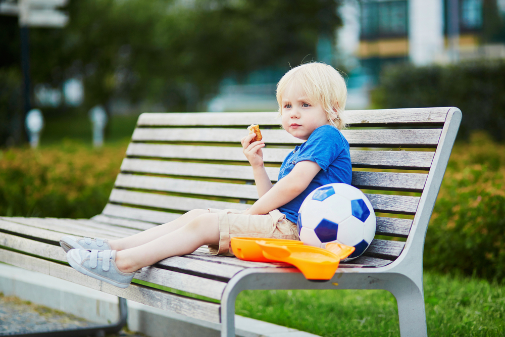 Adorable little boy sitting on the bench with lunchbox in park