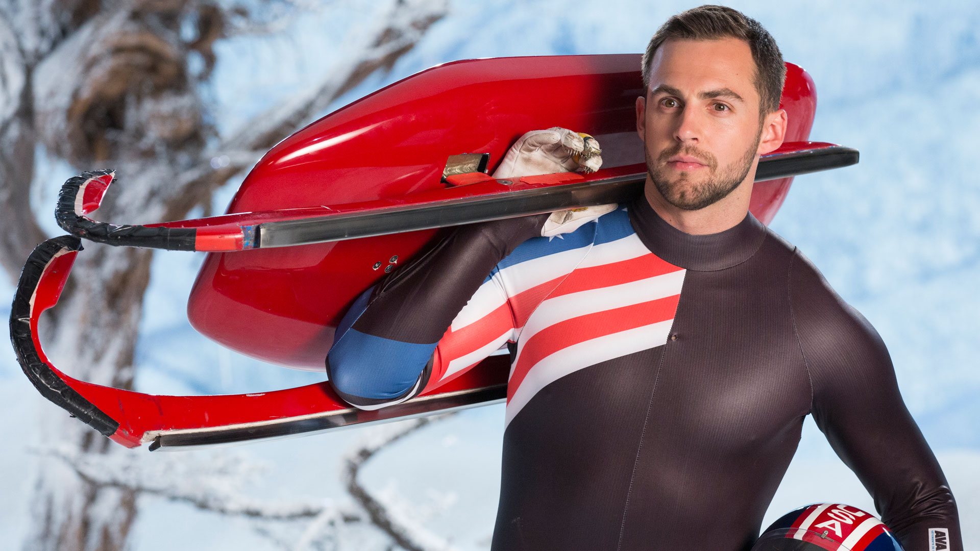 Mazdzer posing with his bobsled